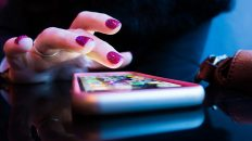 Mujer interacruando con su celular que reposa en una mesa