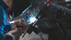 Personas soldando una pieza de metal