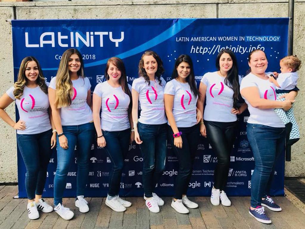 Mujeres posando frente a un cartel de Latinity