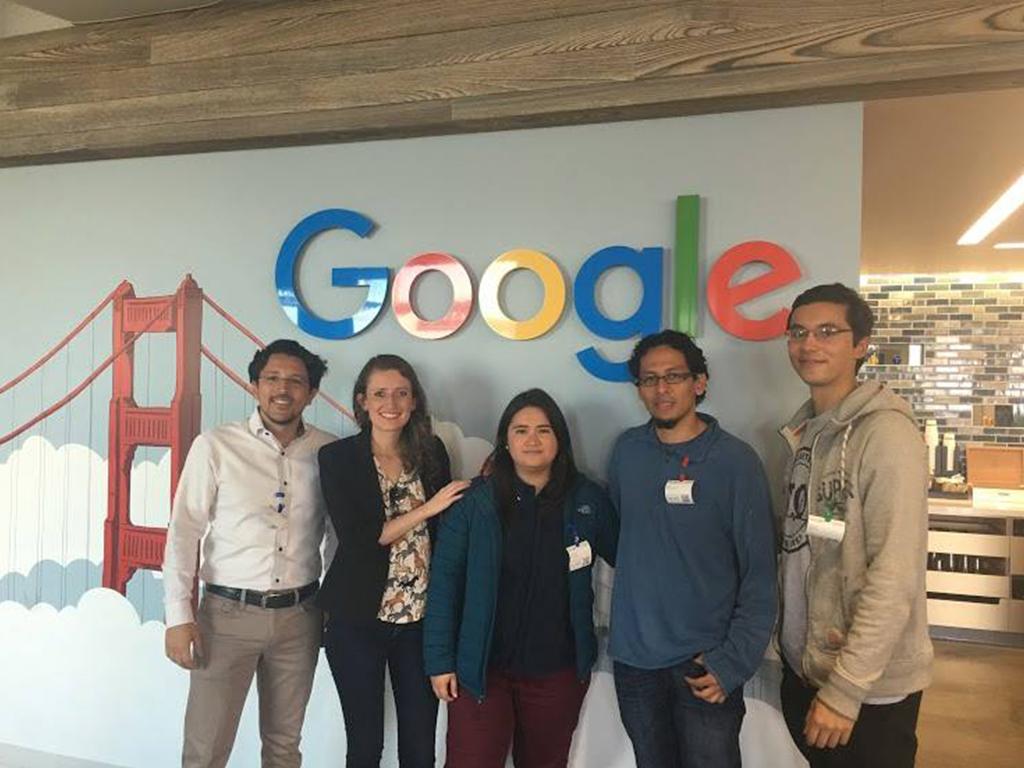 Grupo de personas en frente de una pared con el logo de Google