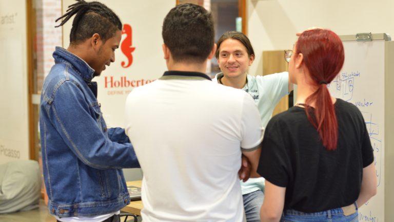 Cuatro personas hablando en la sede de Holberton Medellín