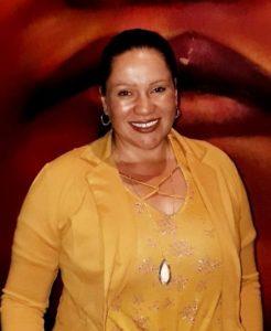 Mujer sonriendo mientras mira a la cámara. Inclusión de personas sordas.