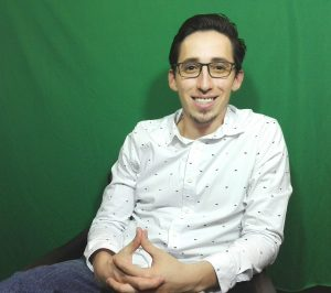 Hombre sonriendo sentado frente a la cámara. Inclusión de personas sordas.