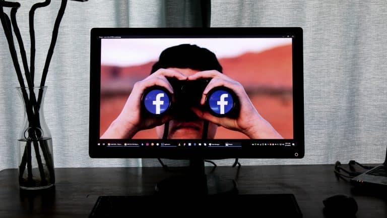 Pantala de un computador que muestra a una persona mirando por unos binoculares con el logo de Facebook
