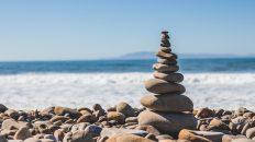 Piedras apiladas de manera equilibrada con el mar de fondo