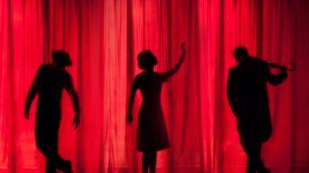Tres siluetas de personas detrás de una cortina roja. Teatro para la inclusión de personas sordas