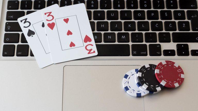 Cartas y fichas de poker encima del teclado de un portátil. Juego online
