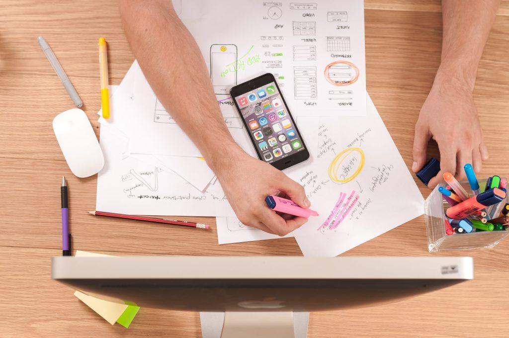 Persona dibujando bocetos y un celular. Empleabilidad